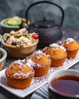 Cupcakes semplici guarniti con zucchero in polvere serviti per la preparazione del tè