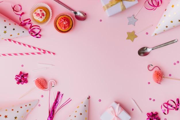 Cupcakes; streamer; cannucce; puntello; cucchiaio; candela; scatole da regalo; coriandoli e cappello di partito su sfondo rosa