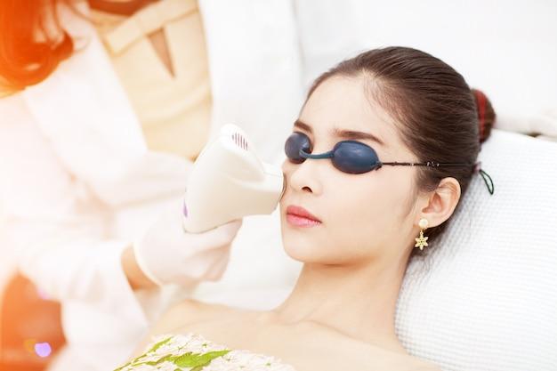 Cura del viso. depilazione laser facciale. estetista giving laser epilation treatment to young