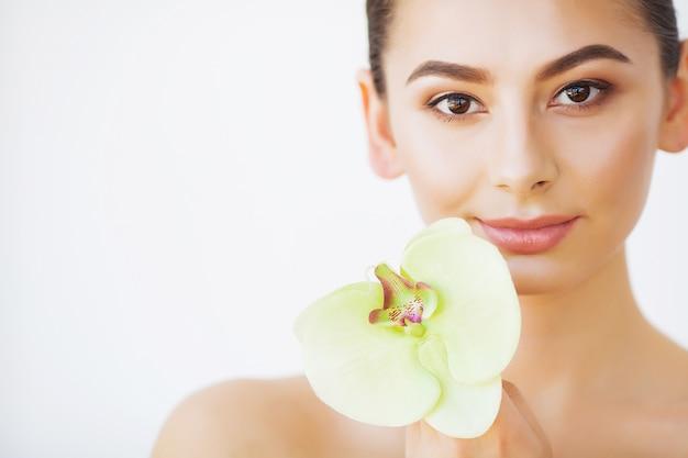 Cura della pelle. bellezza donna, cura e trucco della pelle del viso, fiore orchidea ragazza