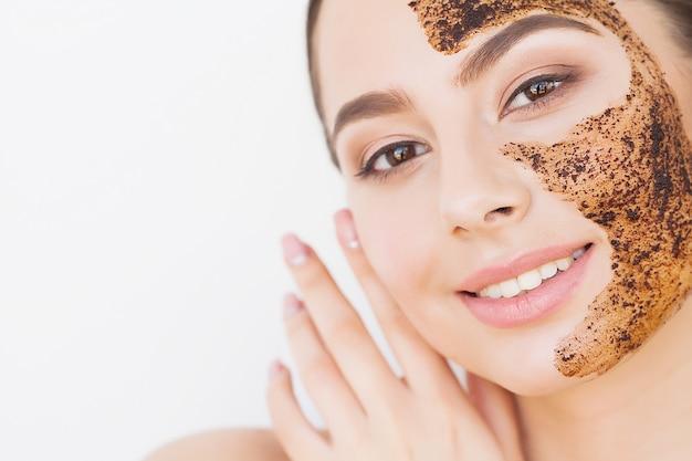 Cura della pelle del viso. giovane ragazza affascinante fa una maschera di carbone nero sul viso
