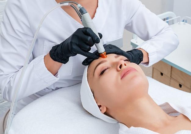 Cura della pelle del viso. primo piano del viso della donna che pulisce alla clinica di cosmetologia, aspirapolvere