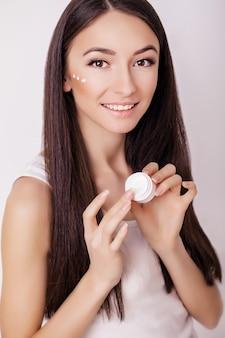 Cura della pelle di bellezza. bella donna felice che applica crema cosmetica sul viso pulito.