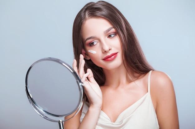Cura della pelle di bellezza. giovane donna con trucco naturale che applica crema