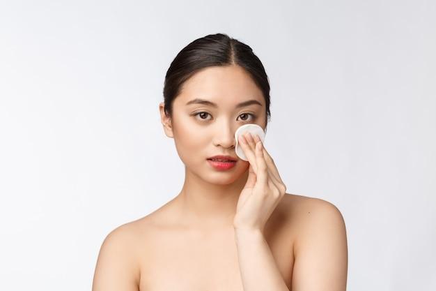 Cura della pelle donna rimozione trucco viso con un tampone di cotone - concetto di cura della pelle primo piano del viso del bellissimo modello di razza mista con una pelle perfetta