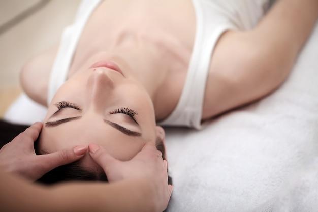 Cura della pelle e del corpo, primo piano di una giovane donna che ottiene il trattamento spa presso il salone di bellezza, spa massaggio viso
