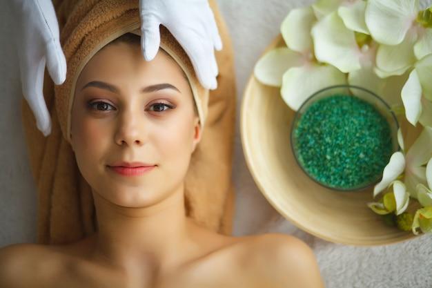 Cura della pelle e del corpo. primo piano di una giovane donna che ottiene trattamento della stazione termale al salone di bellezza. spa face massage. trattamento di bellezza del viso. spa salon