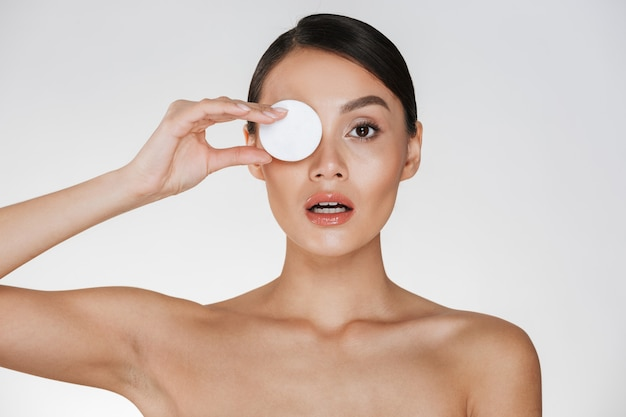 Cura della pelle e trattamento sano della donna che mette il batuffolo di cotone sul suo occhio mentre rimuovendo i cosmetici dal suo fronte, isolato su bianco