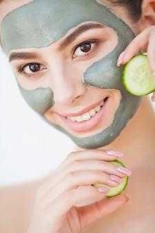 Cura della pelle. giovane donna con cosmetici clay mask holding cetriolo nel suo bagno