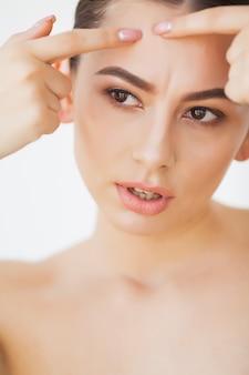 Cura della pelle. la giovane donna prova a rimuovere il suo brufolo