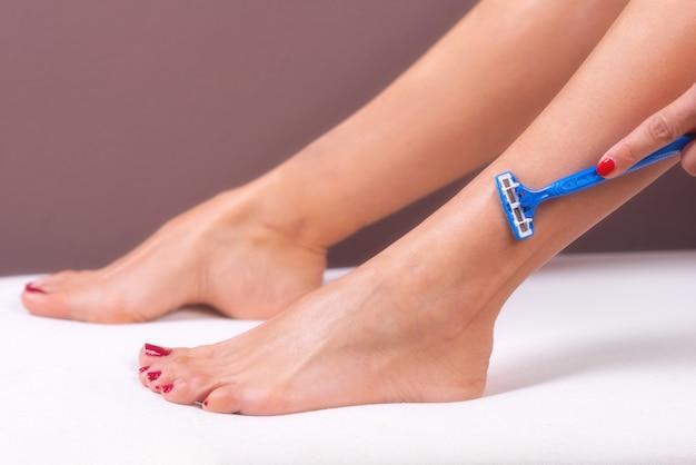 Cura della pelle. rimozione peli. donna che rade le sue gambe con il rasoio