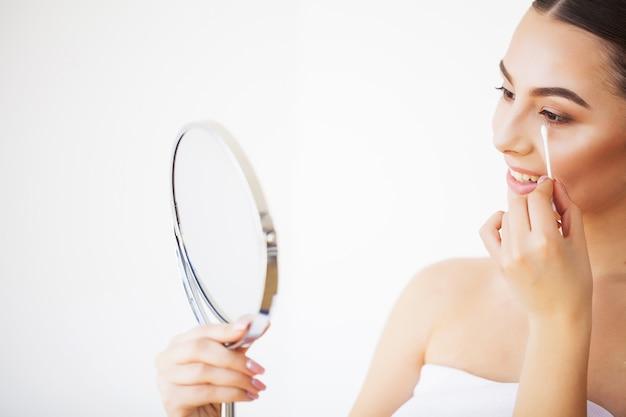 Cura della pelle. ritratto di giovane donna sexy con pelle sana fresca guardando nello specchio al chiuso