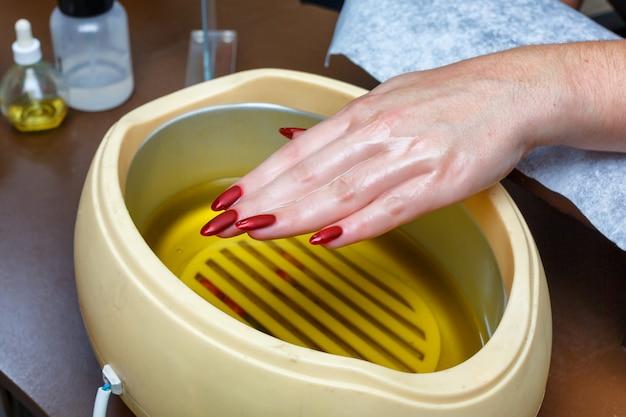 Cura delle mani con cera calda, copertura con cera, salone per manicure.