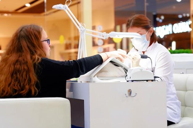 Cura delle unghie delle dita da parte di un esperto di manicure nel salone di bellezza. manicurista dipinge le unghie con lo smalto per unghie.