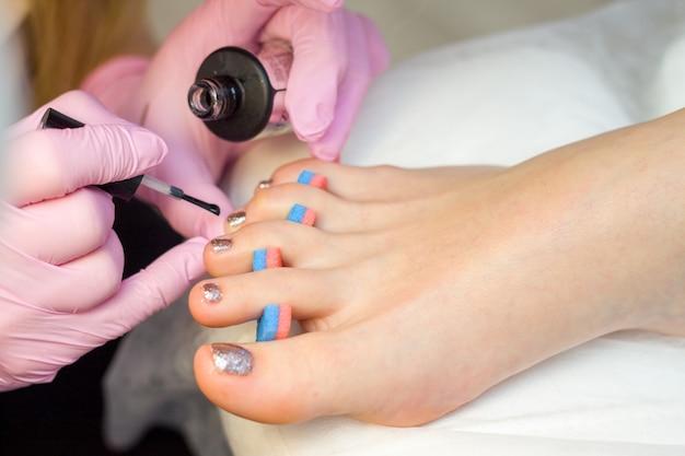 Cura delle unghie e concetto di pedicure. le mani del manicure di primo piano nei guanti rosa sta dipingendo lo smalto dell'oro sulle dita del piede del cliente.