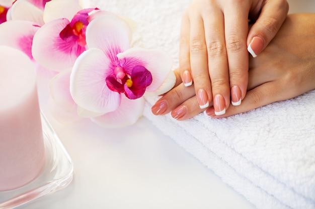 Cura delle unghie. le unghie della bella donna con il manicure francese