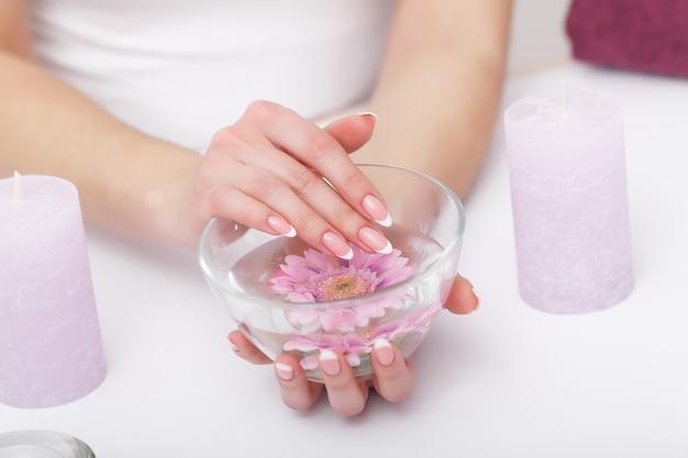 Cura delle unghie. primo piano di belle mani della donna con le unghie naturali nel salone di bellezza. unghia femminile in ammollo in una ciotola di vetro trasparente pieno d'acqua al chiuso. spa manicure concept. alta risoluzione