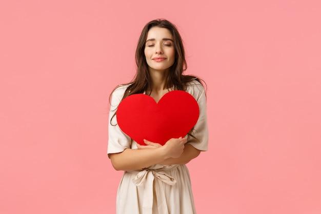 Cura, tenerezza e concetto di bellezza. giovane ragazza tenera e adorabile in vestito che controlla parete rosa, abbracciando la grande carta del cuore con gli occhi chiusi e il sorriso sveglio, stando parete rosa