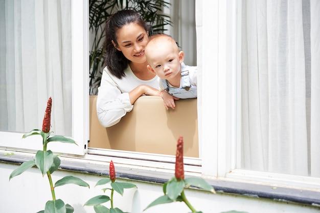 Curioso bambino guardando fuori dalla finestra