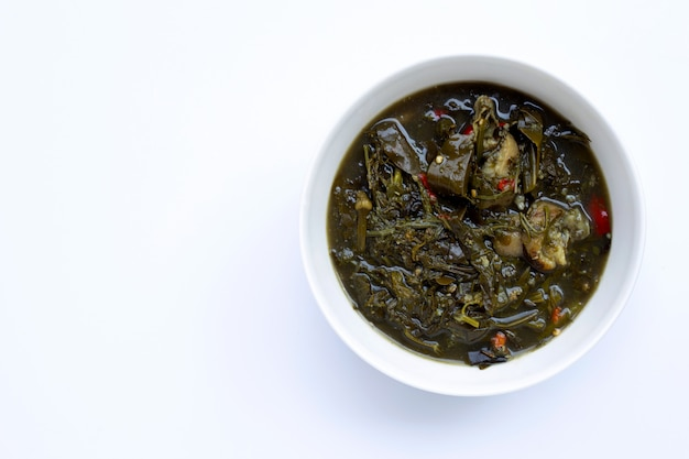 Curry della cassia con carne di maiale su fondo bianco.