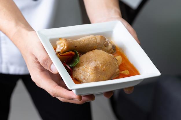 Curry di massaman di pollo sulla mano del cuoco unico