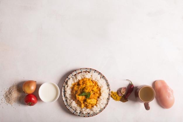 Curry di pollo con riso e gli ingredienti sul tavolo bianco