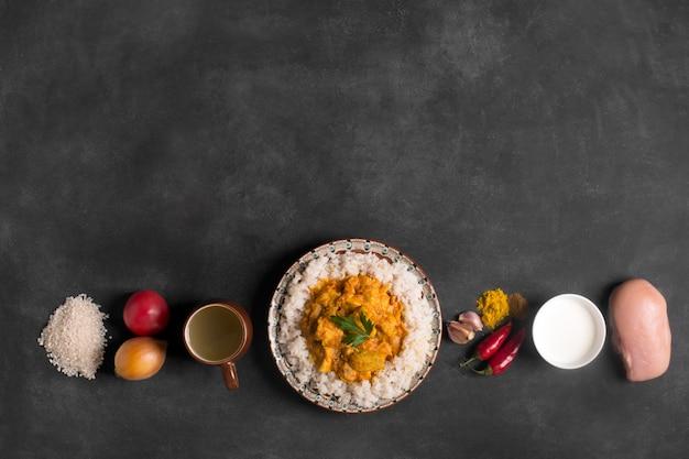 Curry di pollo con riso e ingredienti sulla lavagna nera. vista dall'alto copia spazio. orientamento orizzontale