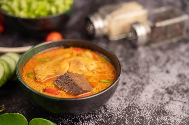 Curry di pollo in una tazza nera.