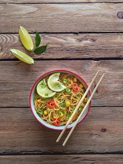 Curry piccante al cocco con spaghetti di riso e verdure dell'orto.