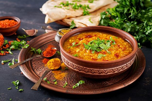 Curry piccante indiano dhal in ciotola, spezie, erbe, fondo di legno nero rustico.