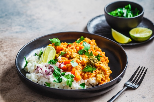 Curry vegetariano della lenticchia con riso in banda nera. concetto di cibo sano vegan.