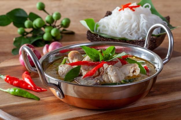 Curry verde con il pollo su fondo di legno, cucina tailandese