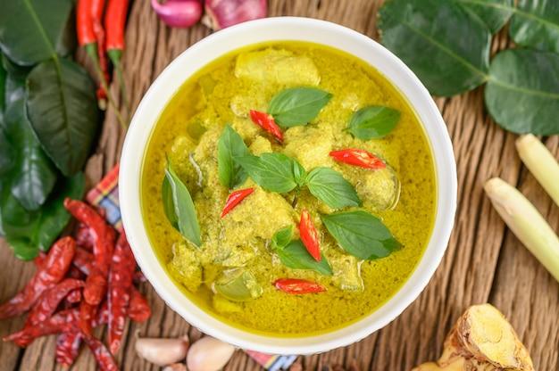Curry verde in una ciotola con foglie di lime, cipolla rossa, citronella, aglio e kaffir lime