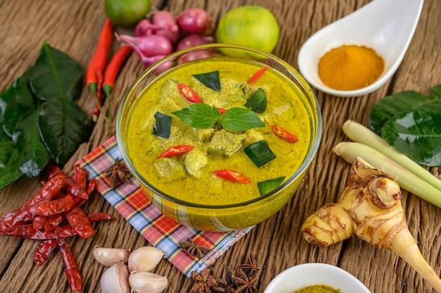 Curry verde in una ciotola e spezie sulla tavola di legno.