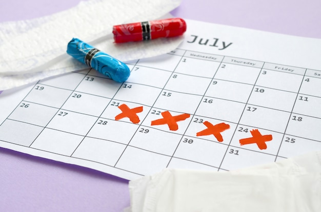 Cuscinetti mestruali e tamponi sul calendario del periodo mestruale con segni di croce rossa
