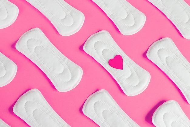 Cuscinetti mestruali femminili su fondo rosa, salute della donna, concetto del ciclo dei periodi della donna