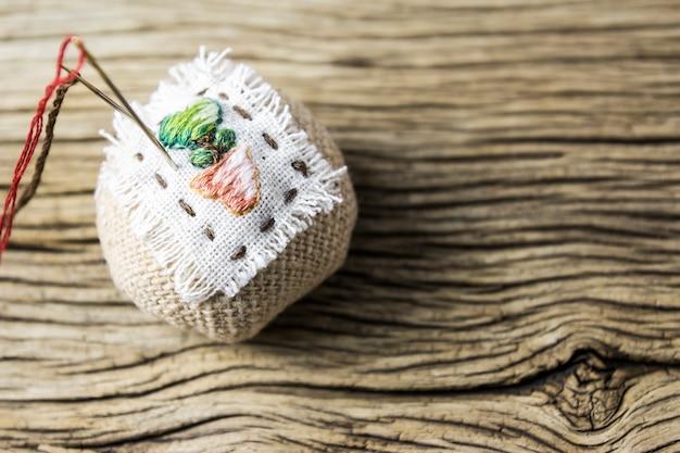 Cuscinetto a spillo sul vecchio tavolo di legno