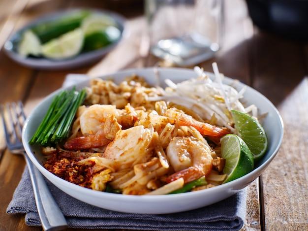 Cuscinetto di gamberetto tailandese sul piatto con l'erba cipollina e le arachidi