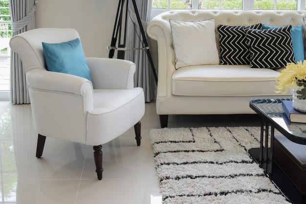 Cuscini bianchi e blu su un divano in pelle bianca nel salotto d'epoca