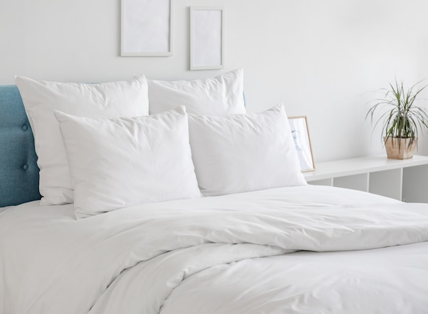 Cuscini bianchi e piumone sul letto blu.