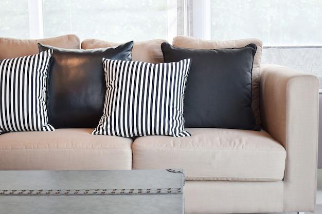 Cuscini in pelle nera e strisce sul divano beige in velluto nel moderno salotto in stile industriale