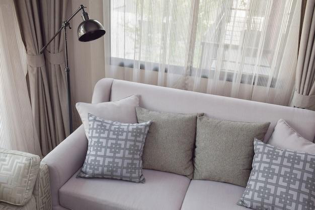 Cuscini modello e texture sul divano beige nel soggiorno