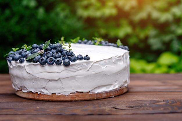 Cuscino appetitoso del biscotto della torta di cheesecake decorato mirtilli bianchi crema e supporti di menta sulla tavola rustica blu di legno