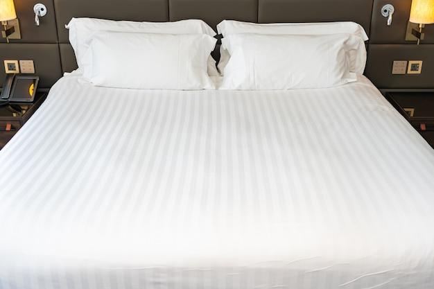 Cuscino bianco sull'interno della decorazione del letto della camera da letto