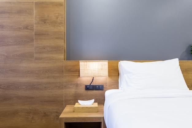 Cuscino bianco sulla decorazione del letto con lampada e scatola del tessuto all'interno della camera d'albergo