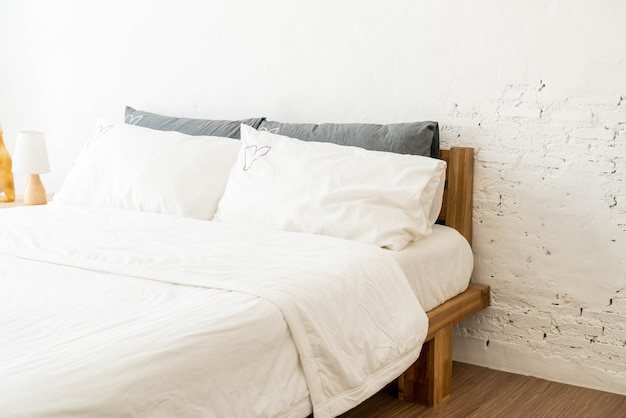 Cuscino bianco sulla decorazione del letto in camera da letto