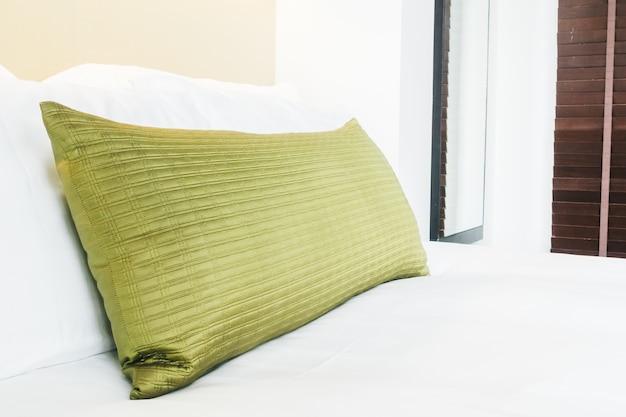 Cuscino d'oro sul letto con lenzuola bianche