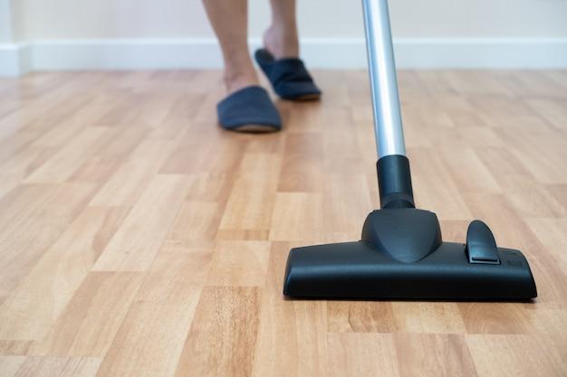 Custode della casa che utilizza la macchina del vuoto per pulire un pavimento di legno.