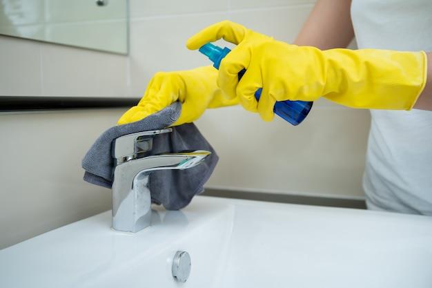 Custode della donna che pulisce un rubinetto di acqua inossidabile sporco sul lavandino nella toilette. cameriera che spruzza soluzione detergente liquida sul rubinetto sporco in bagno e usando un panno in microfibra su una linguetta per l'acqua.