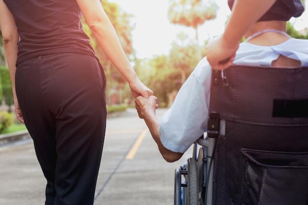 Custode e figlia con paziente in sedia a rotelle